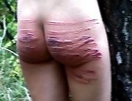 Hot russian brunette bound to a tree for a brutal caning