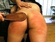 Liz`s ever-reddening butt endures a spanking, a caning, and a paddling